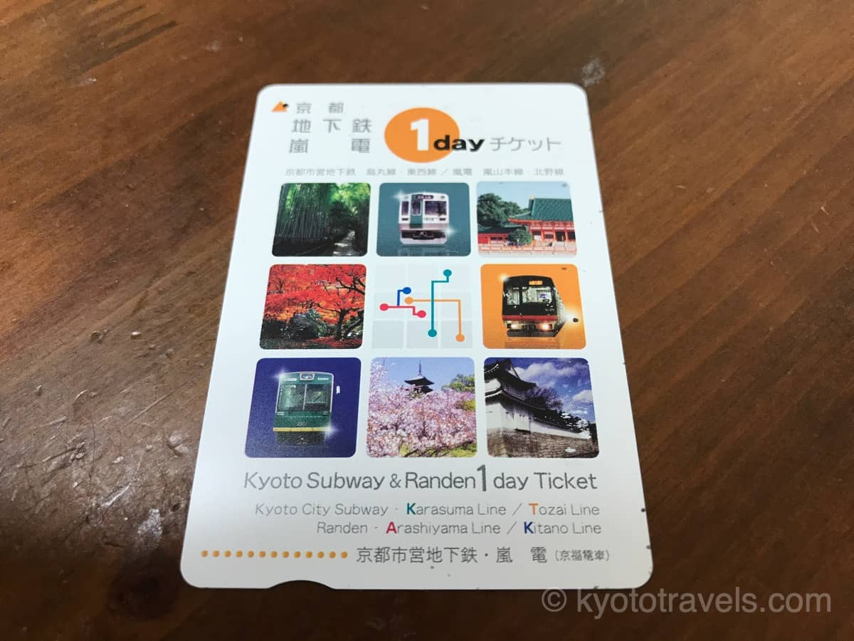 地下鉄・嵐電の1日乗車券が木製のテーブルに置かれています