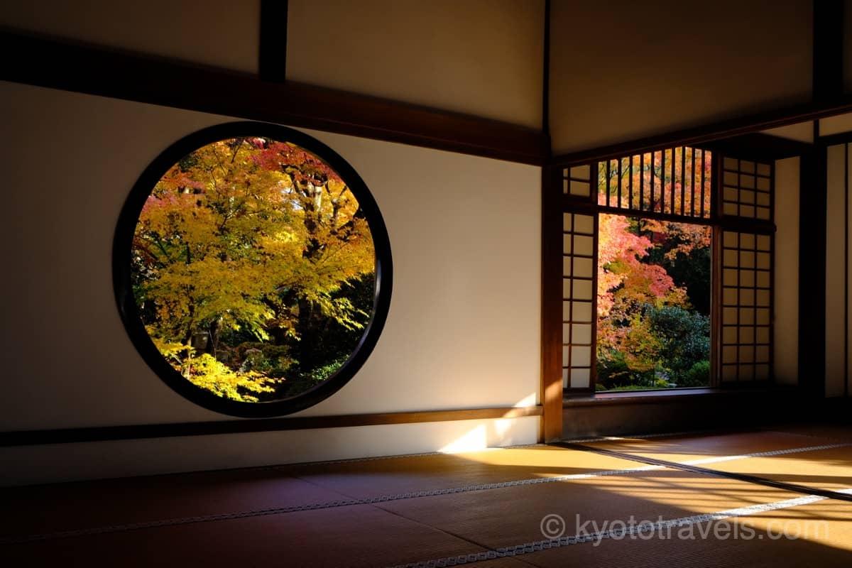 紅葉に朝日の差し込む源光庵の丸い窓と四角い窓