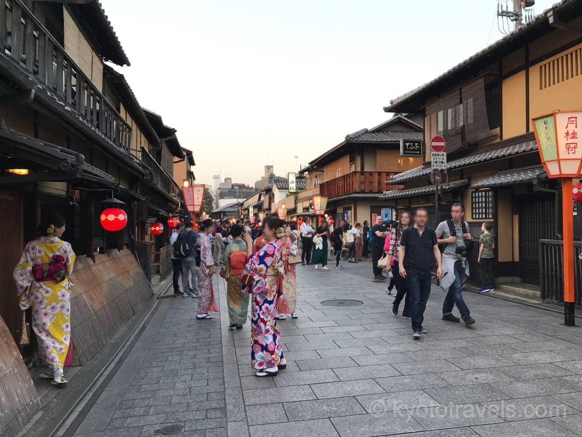 祇園の大通りに着物を着た女性や外国人観光客が歩いています。