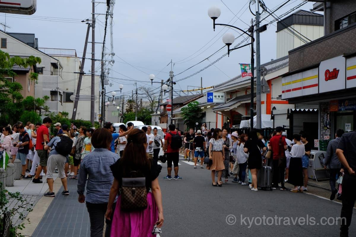 伏見稲荷駅の前の道路に観光客が溢れています