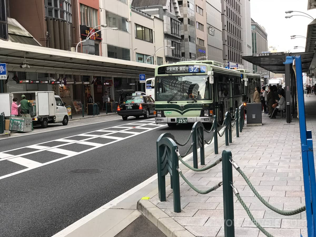 四条通のバス停に緑色の市バスが停車しています。